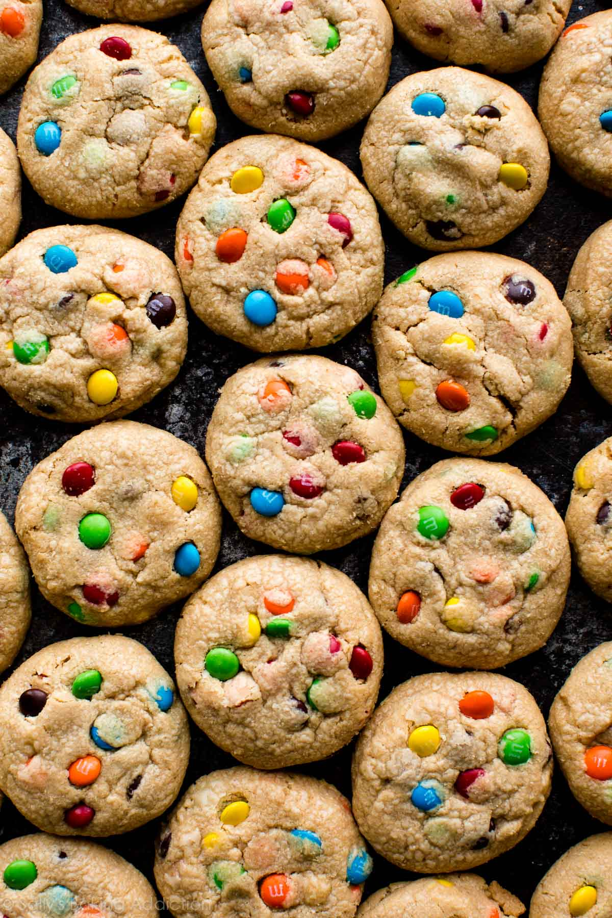 Softest peanut butter cookies! Filled with M&M candies! Recipe on sallysbakingaddiction.com