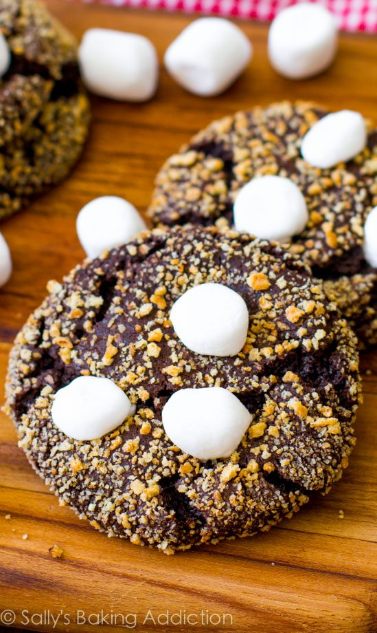 S'mores Cookies! Soft, chewy chocolate crinkle cookies rolled in graham cracker and topped with marshmallows. @sallybakeblog