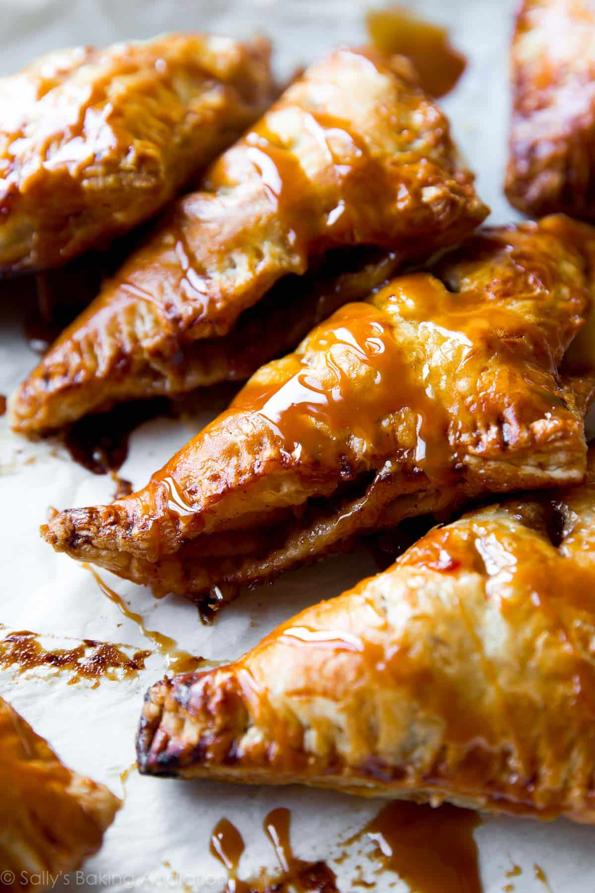 Super easy, flaky hot apple turnovers with delicious salted caramel on top! Recipe on sallysbakingaddiction.com