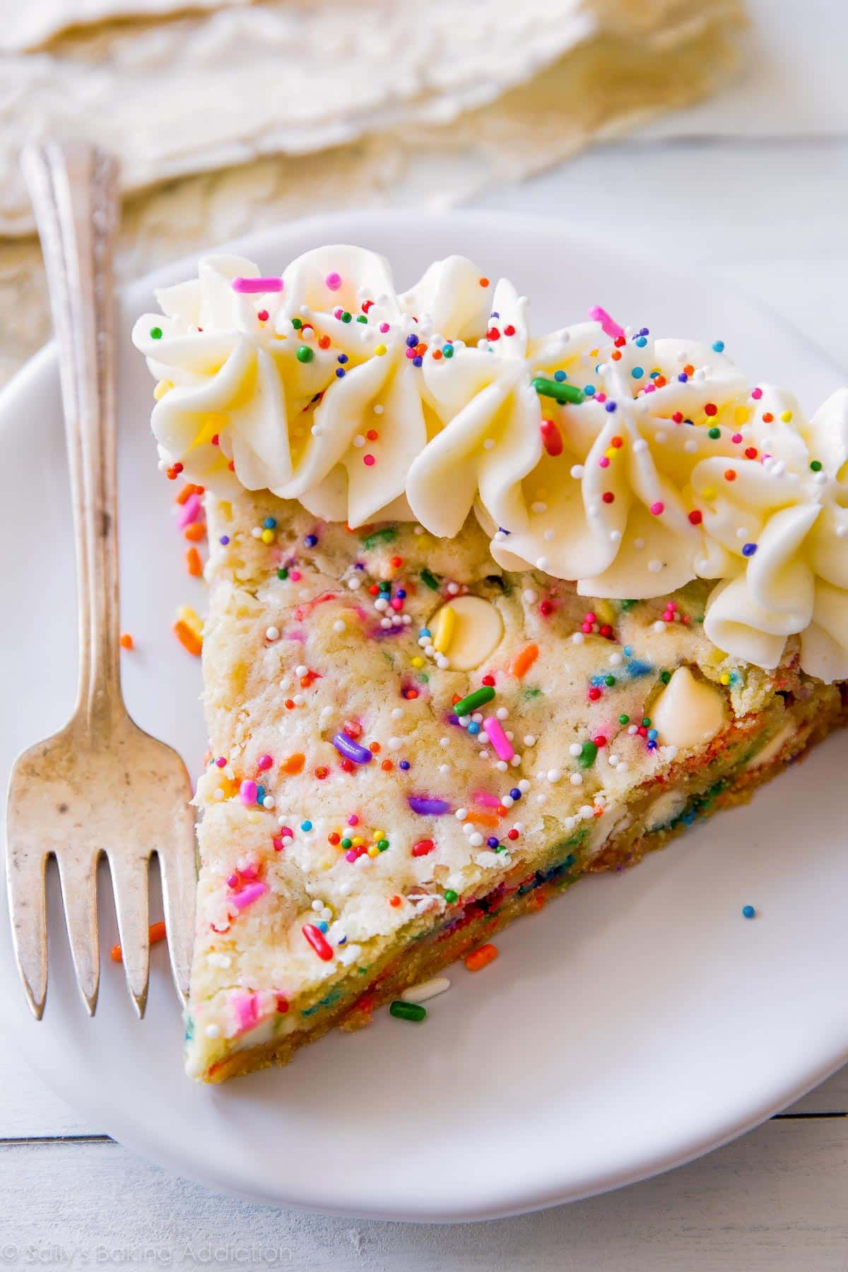 Funfetti sugar cookie cake topped with vanilla almond frosting! Soft-baked cookie pizza with lots of rainbow sprinkles! Recipe on sallysbakingaddiction.com