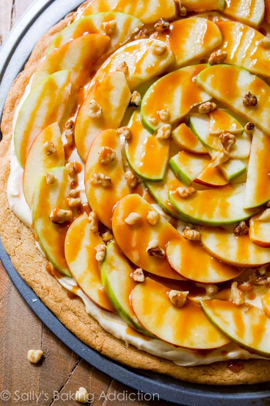 This apple dessert pizza with caramel cream cheese frosting is a show stopped! It's simple to make and it's all prepared on a snickerdoodle cookie crust!