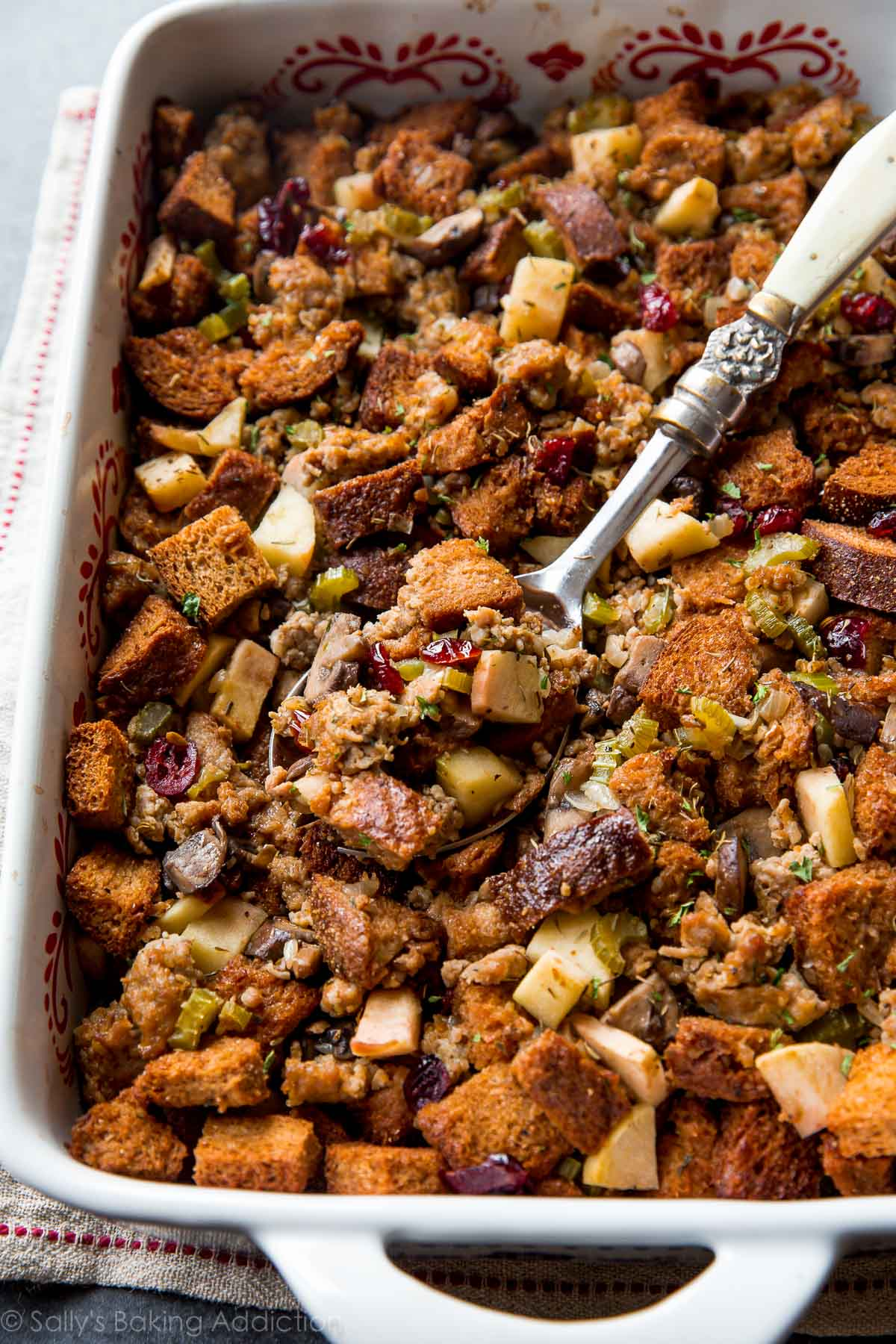 The BEST Thanksgiving dressing recipe! With apples, sausage, savory herbs, mushrooms, and whole grain bread. Recipe on sallysbakingaddiction.com