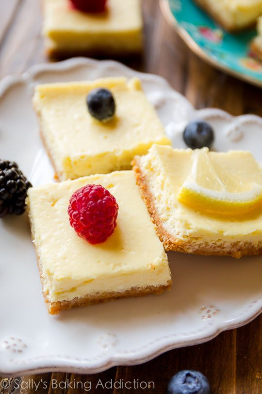 Creamy and tangy lemon bars made with Greek yogurt-- only 130 calories per lemon square! Easy recipe on sallysbakingaddiction.com