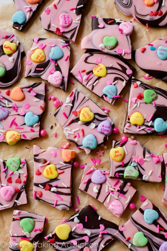 Super simple chocolate bark swirled with pink white chocolate and topped with lots of candy hearts! Easy recipe found on sallysbakingaddiction.com