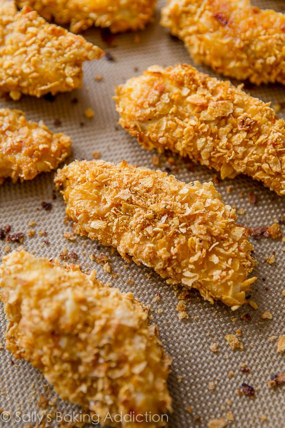 EXTRA crispy and baked buffalo chicken fingers! Coated in cornflakes for extra crunch. Recipe on sallysbakingaddiction.com