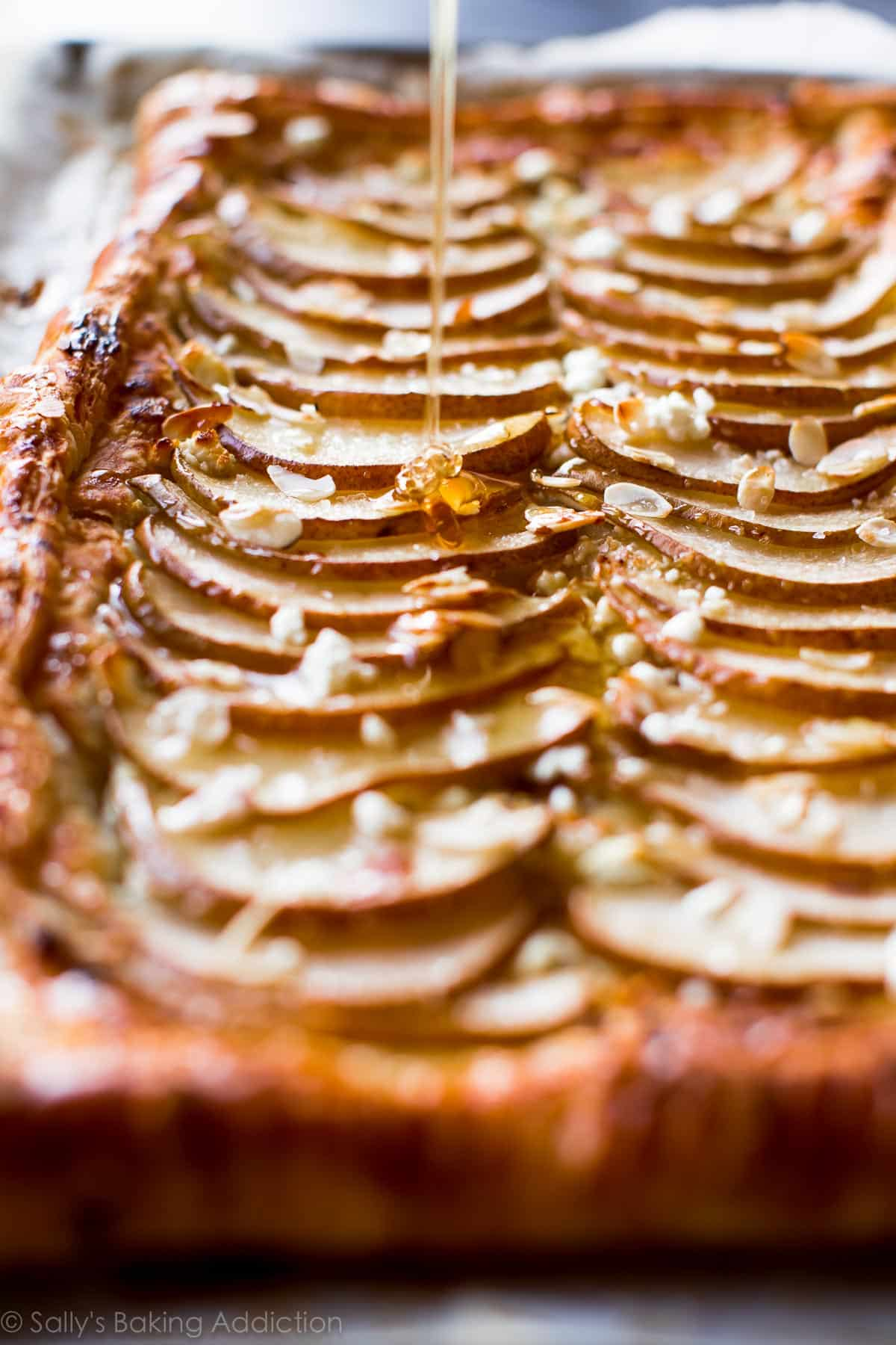 Sweet and salty, super easy honey pear tart with goat cheese, honey, and toasty almonds! Recipe on sallysbakingaddiction.com