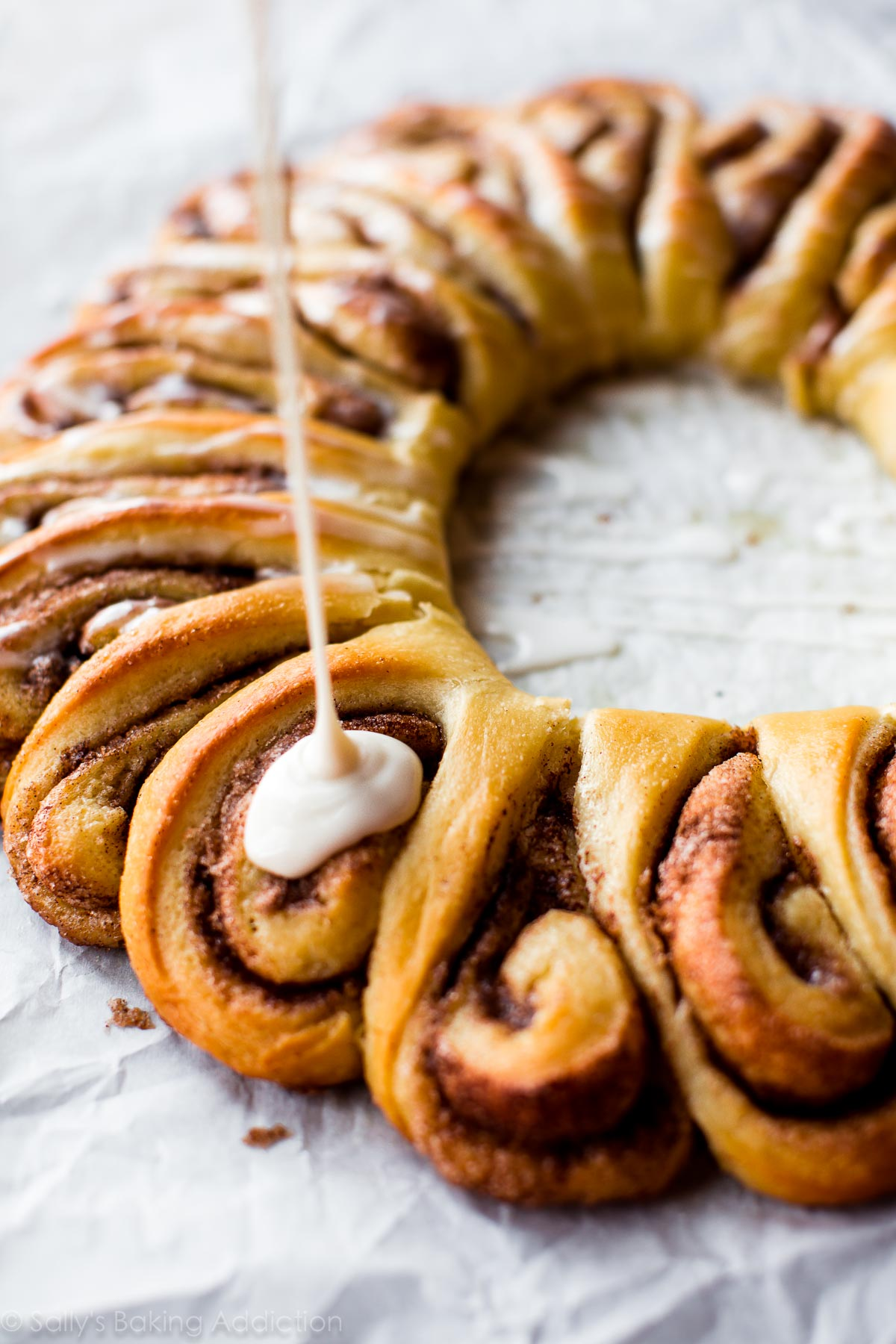 Learn how to make a warm and fluffy, ooey gooey cinnamon roll wreath! Recipe on sallysbakingaddiction.com