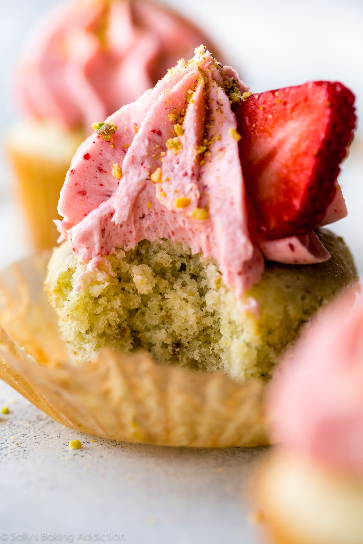 Deliciously simple from-scratch pistachio cupcakes with creamy strawberry frosting! Recipe on sallysbakingaddiction.com