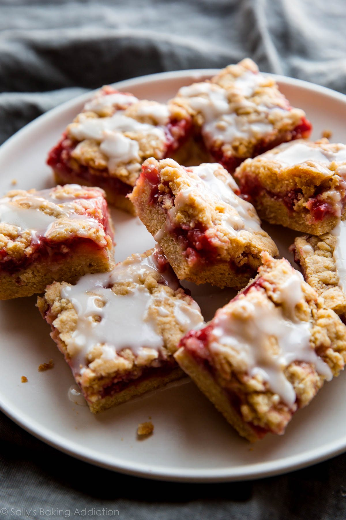 Lemon strawberry crumb bars bring some blissful sunshine inside with a buttery crust and topping, fresh strawberries, and sweet lemon glaze! Recipe on sallysbakingaddiction.com