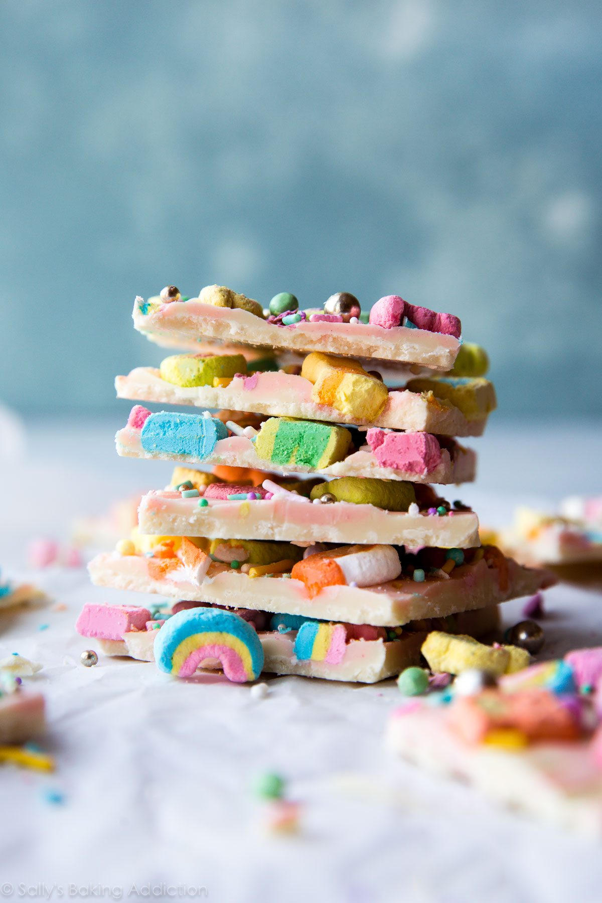 Magical lucky charms bark with only 3 ingredients! White chocolate, lucky charms marshmallows, and sprinkles! Easy candy recipe on sallysbakingaddiction.com