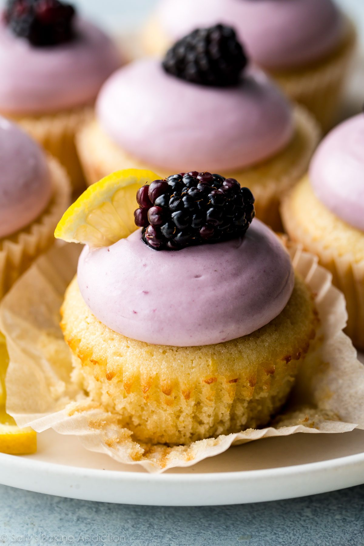 These lemon cupcakes are soft, fluffy, and exploding with lemon flavor! Topped with fresh blackberry cream cheese frosting! So pretty! Recipe on sallysbakingaddiction.com