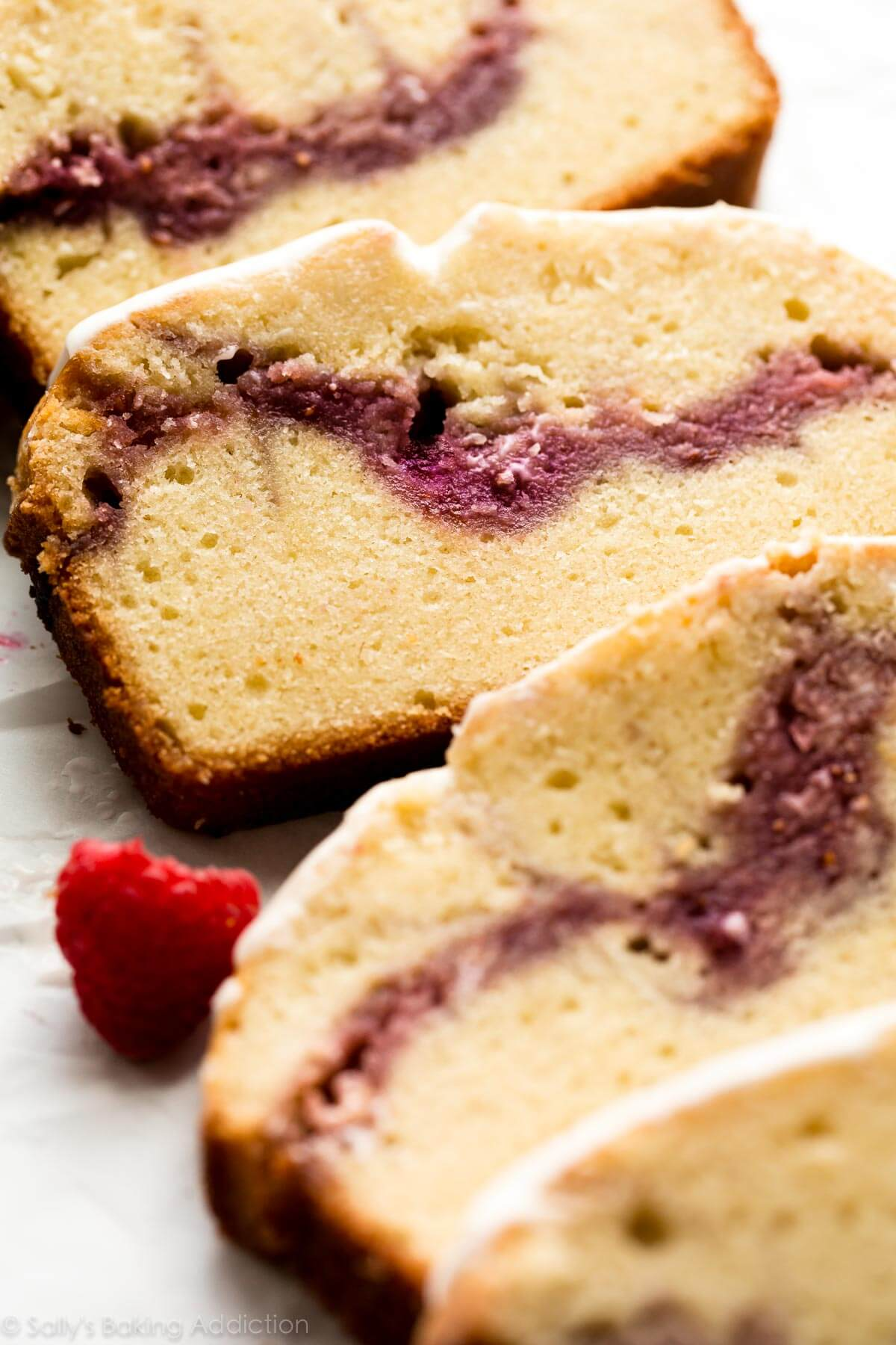Deliciously moist and buttery pound cake with a thick raspberry swirl! Topped with icing and SO EASY to make! Recipe on sallysbakingaddiction.com