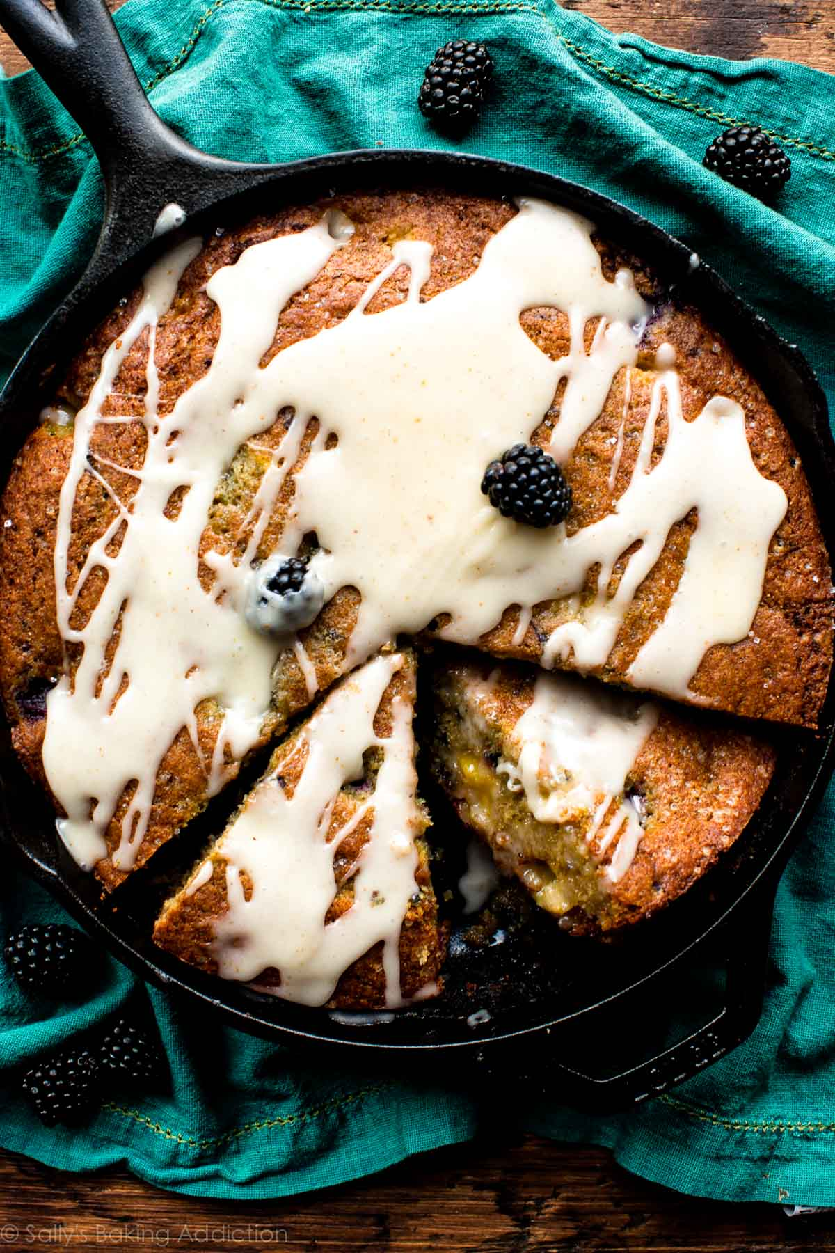 Cornmeal and summer fruit provide a lovely texture to this moist blackberry peach skillet cornmeal cake. Top with brown butter icing for the ultimate treat! Recipe on sallysbakingaddiction.com