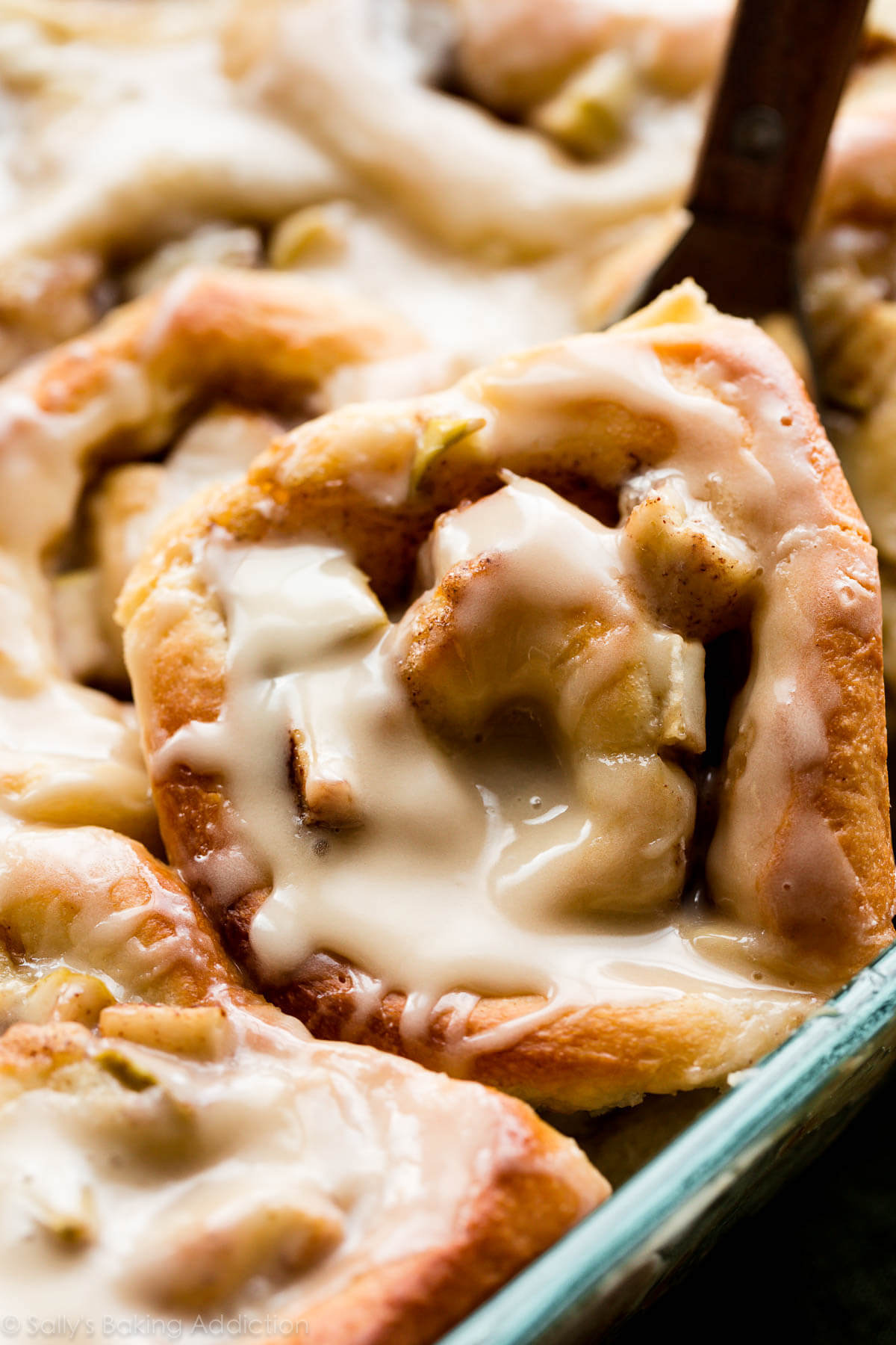 Fresh out of the oven, warm and gooey apple cinnamon rolls with delicious caramel icing on top! Recipe on sallysbakingaddiction.com