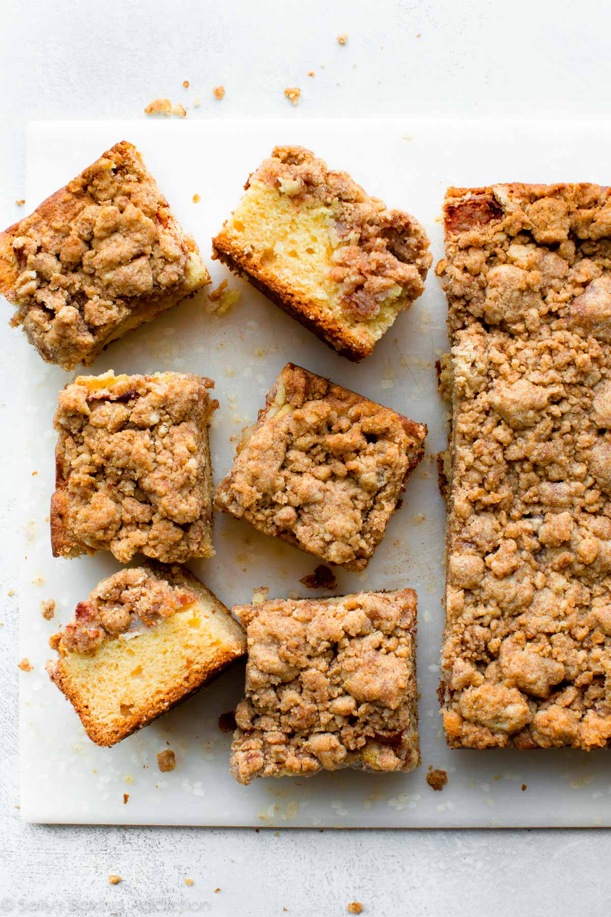 Delicious New York style crumb cake with warm cinnamon apples and DOUBLE the buttery crumb topping! Recipe on sallysbakingaddiction.com
