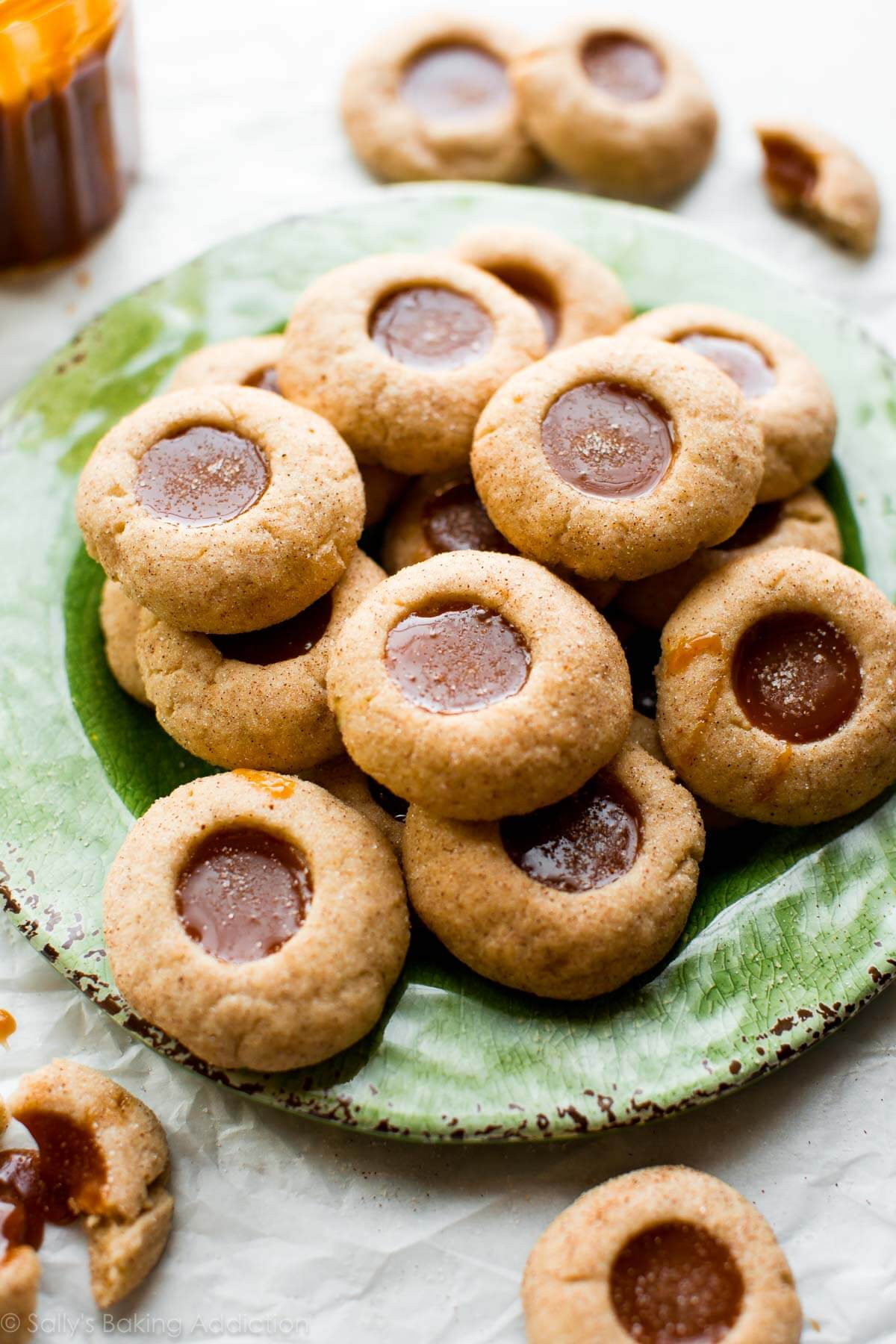Apple spice thumbprint cookies filled with homemade caramel! These delicious fall cookies are completely irresistible and so simple to make! Recipe on sallysbakingaddiction.com