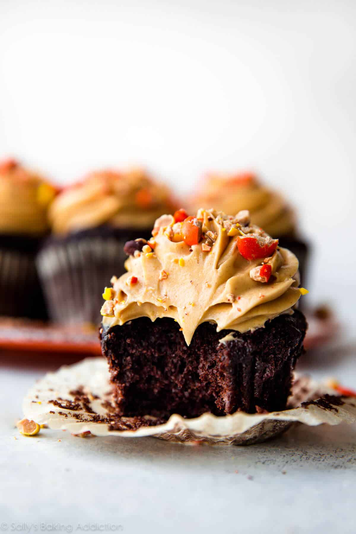 Rich, moist, and super dark chocolate cupcakes topped with creamy peanut butter frosting and Reese's Pieces! Recipe on sallysbakingaddiction.com