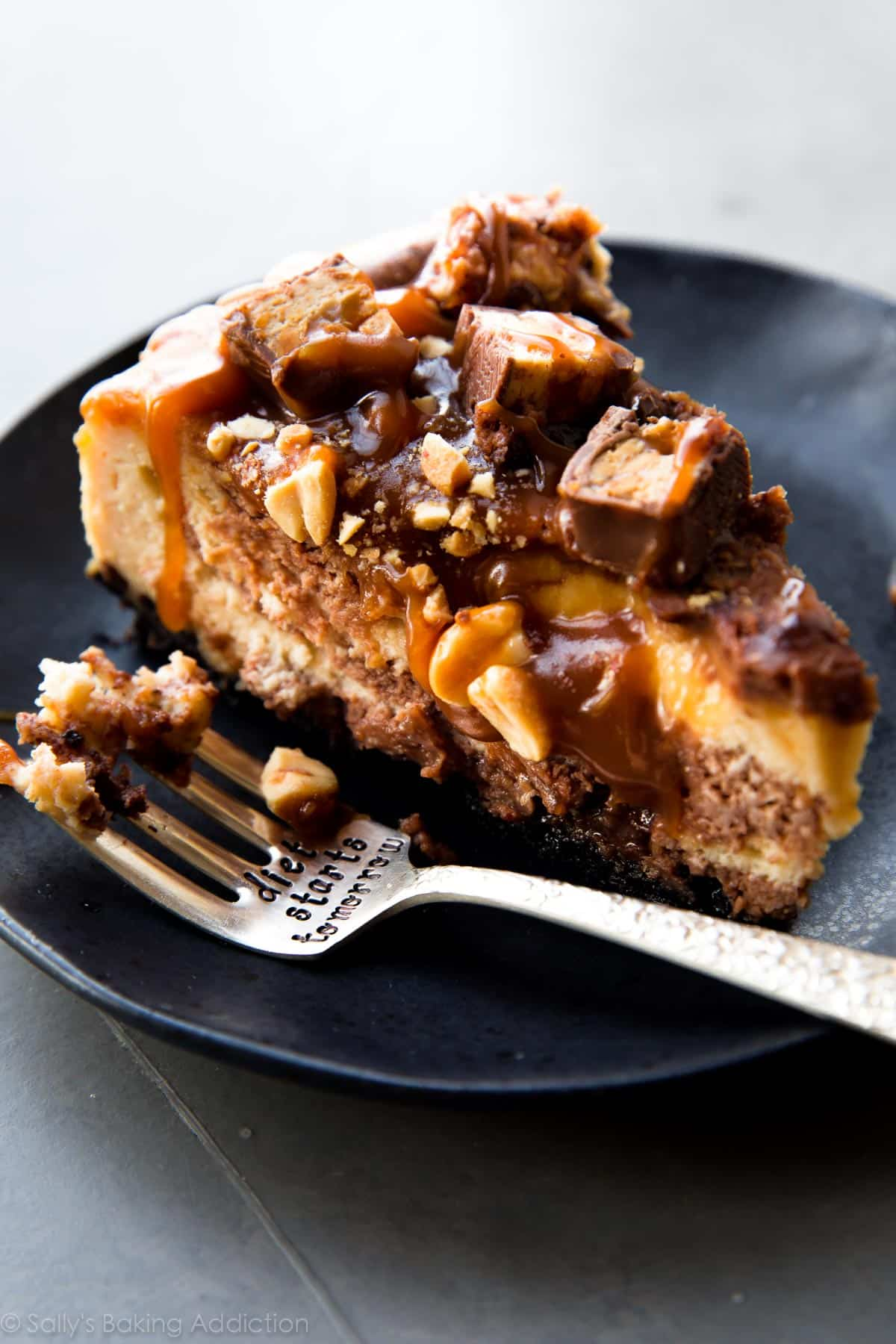 Super decadent and rich Snickers cheesecake with peanut butter and chocolate swirl, salted caramel, peanuts, and Snickers candy bars on top! Recipe on sallysbakingaddiction.com
