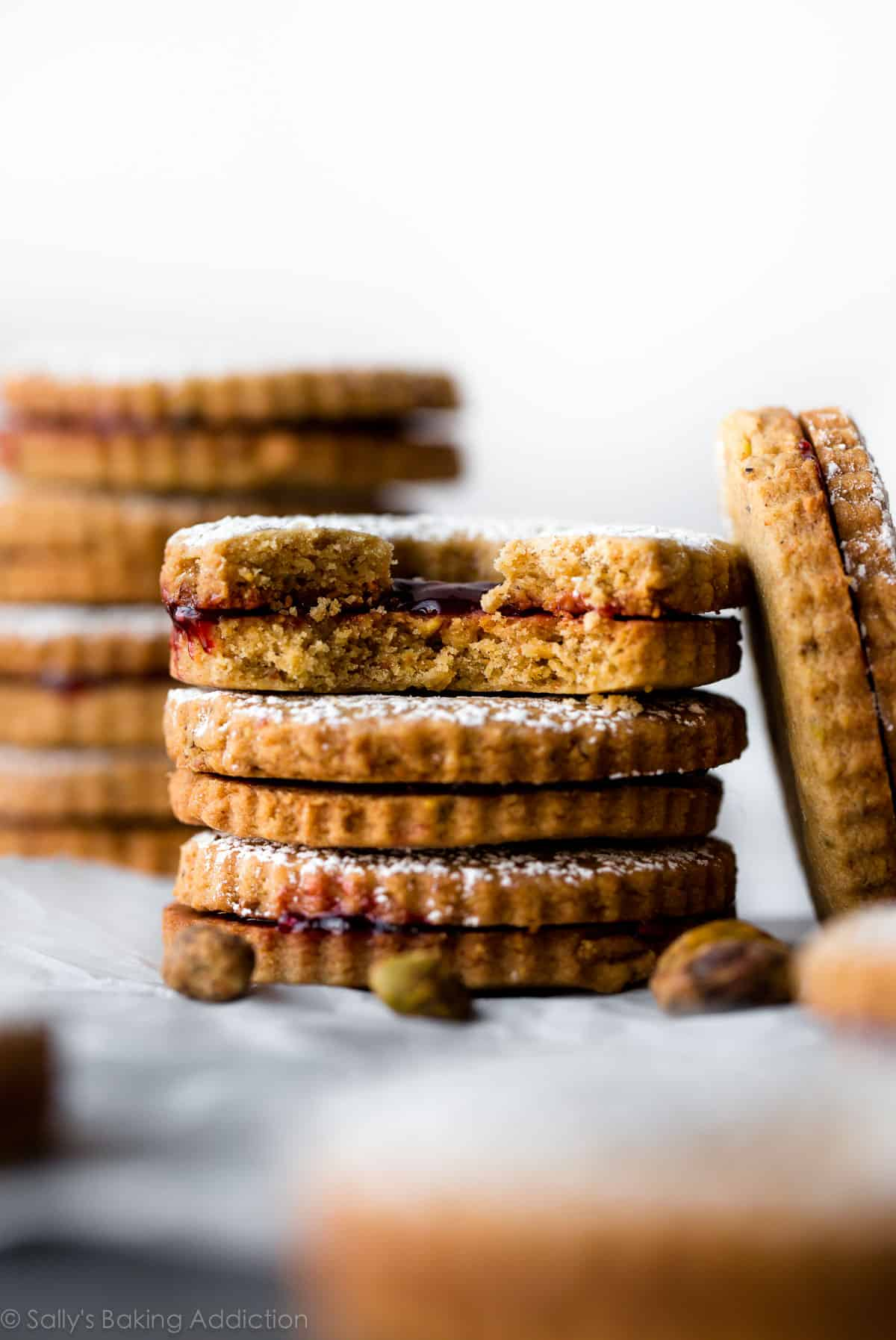 Soft, a little salty, and sweet pistachio linzer cookies filled with delicious raspberry jam! Christmas cookie recipe on sallysbakingaddiction.com