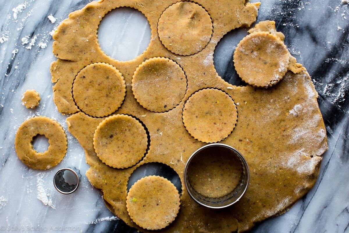 Cutting cookie dough for linzer cookies on sallysbakingaddiction.com
