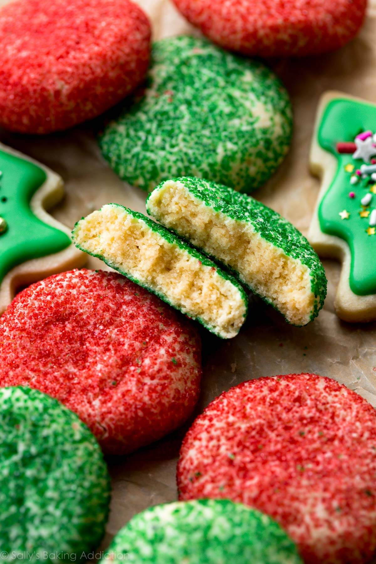 Sparkling green and red cream cheese sugar cookies with the softest, creamiest texture! These Christmas cookies are quick and easy too! Recipe on sallysbakingaddiction.com