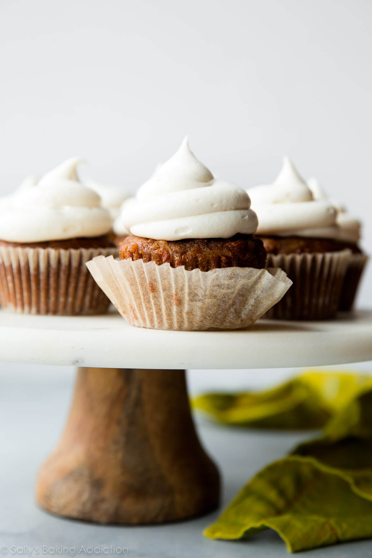 Super spiced and moist carrot cake cupcakes filled with shredded coconut and topped with creamy cream cheese frosting. Recipe on sallysbakingaddiction.com