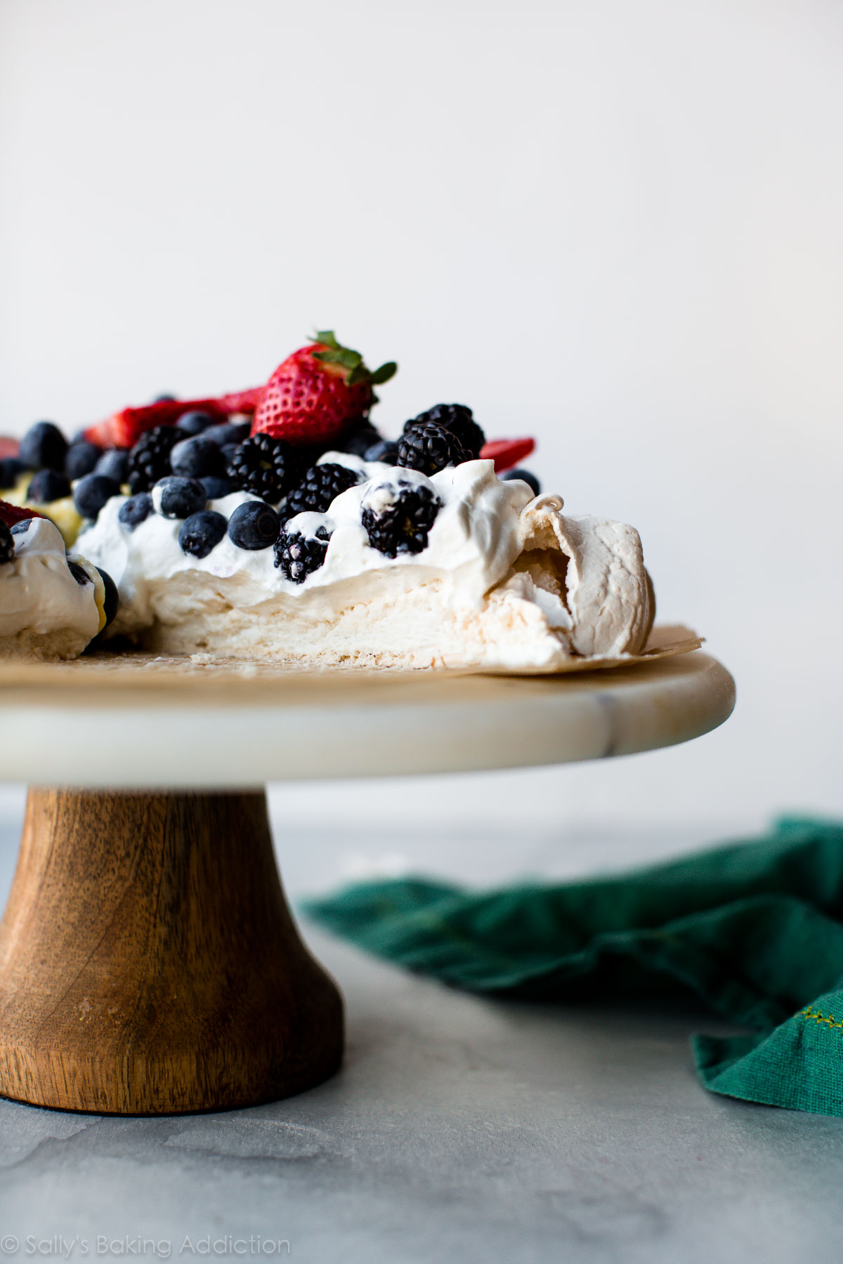 Pavlova is crisp on the edges, chewy on top, and marshmallow soft and creamy in the centers. Pile high with lemon curd, whipped cream, and fresh fruit to make a naturally delicious gluten free dessert! Recipe on sallysbakingaddiction.com