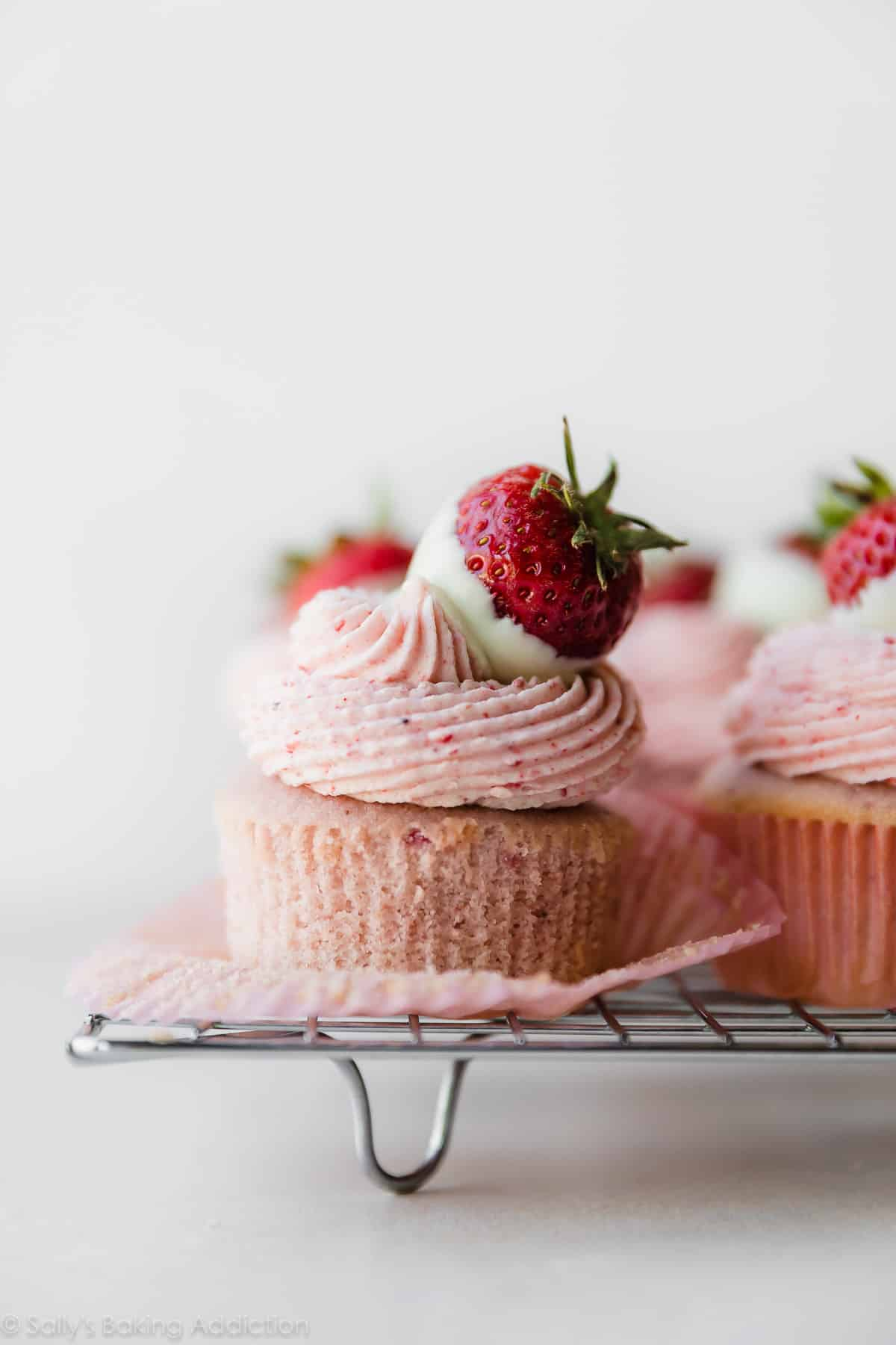 Delicious REAL STRAWBERRY cupcakes made from reduced strawberry puree. Pure strawberry, no artificial flavors. Topped with white chocolate strawberry frosting made from freeze-dried strawberries! Recipe on sallysbakingaddiction.com