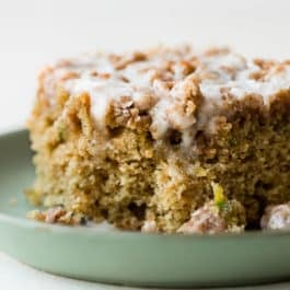 Zucchini crumb cake is moist, spiced with cinnamon, topped with brown sugar crumble, and sweet vanilla icing! You can't even tell you're eating your veggies! Delicious coffee cake recipe on sallysbakingaddiction.com