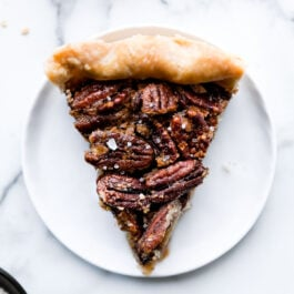 Deliciously salted maple pecan pie with a butter pie crust and made with maple syrup. No corn syrup pecan pie recipe on sallysbakingaddiction.com